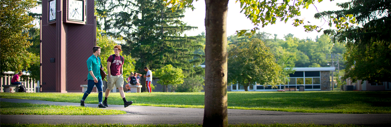 Two students talking and walking through campus. Students in the background talking near the clock tower.